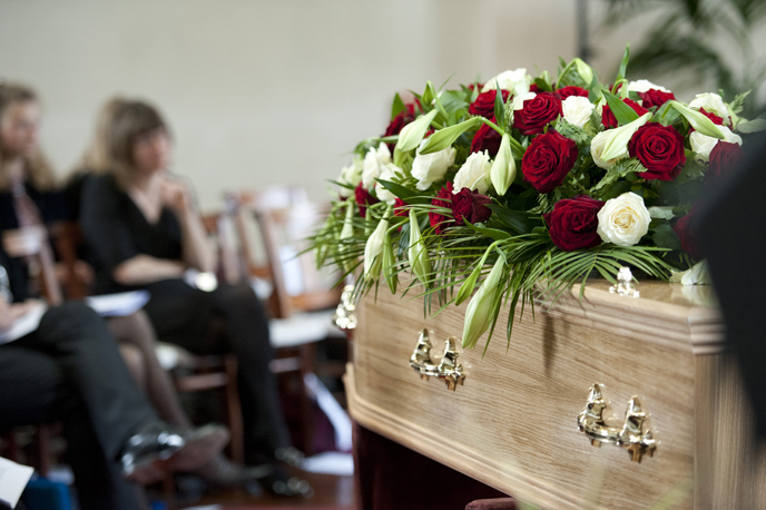 Grieving people look over a wooden casket and flowers